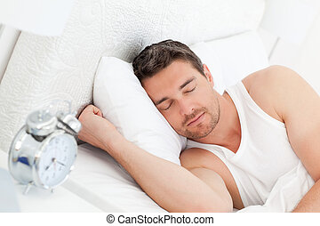 A calm man in his bed before waking up in his bedroom