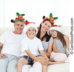 Family during Christmas day looking at the camera at home