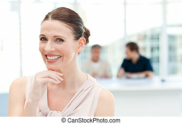 Smiling businesswoman looking at the camera while her...