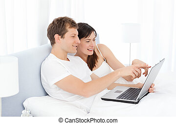 Young pairs watching videos on their computer at home