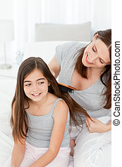 Woman brushing her daughter hair at home