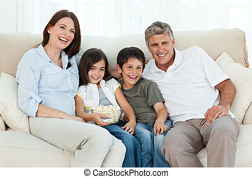 Family watching tv while they are eating popcorn