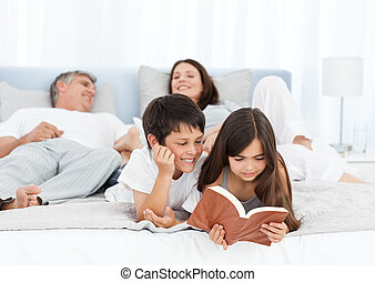 Parents talking while their childrens are reading on the bed...