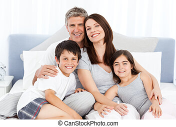 Family lying down on their bed - Family lying down on their...