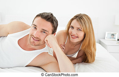 Couple lying down together in their bed at home
