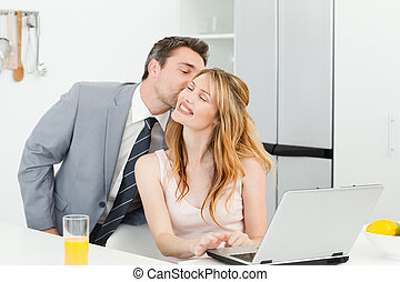 Businessman kissing her girlfriend at home