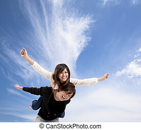 Young Asian Couple smiling under blue sky and cloud