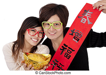 Happy chinese new year. Young couple holding gold ingot and...
