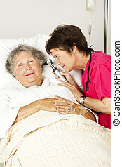Hospital Patient Ear Check - Hospital nurse checking a...