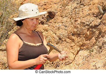 Senior Geologist Woman - Senior woman geologist tap a rock...