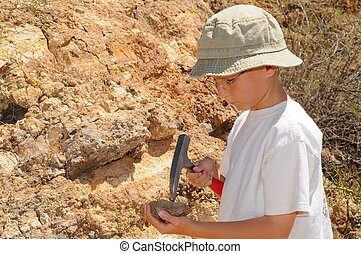 Boy Geology Student - Young boy studing geology out in the...