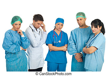 Sad doctors team with problems standing in a row and...