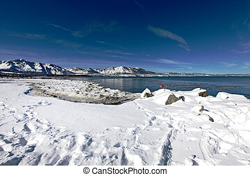 Lake Tahoe with white snow and blue sky