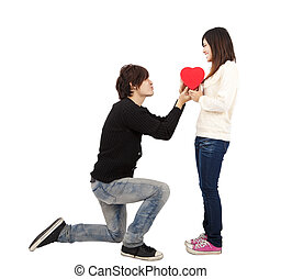 Asian young Man handing over love gift to young woman on...