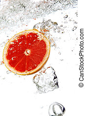 Grapefruit dropped into water - Fresh grapefruit dropped...