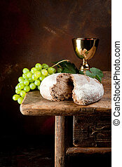 Sacred wine and bread - Sacred wine chalice with grapes and...