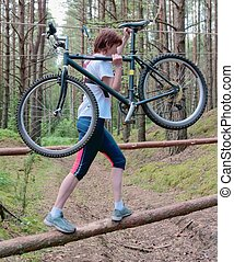The sportswoman transfers a bicycle through an obstacle on...