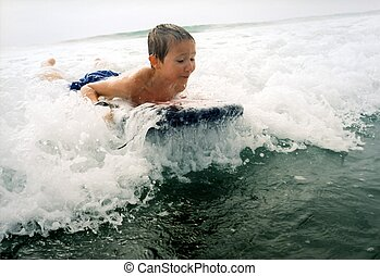 Boy Surfing - Young boy surfing a wave on a boogie board...