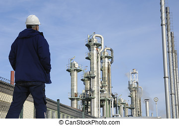 oil worker and industry - chemical worker overlooking oil...