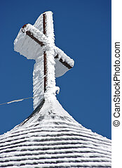 Cross in winter after snowstorm