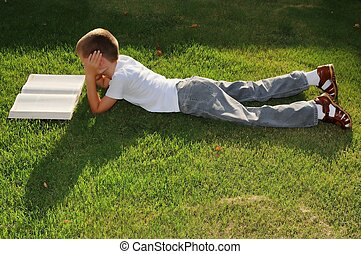Boy Reading Outside - Young boy outdoors on the grass...
