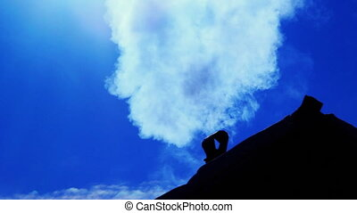 Smoking old chimney on the backdrop of clear blue sky