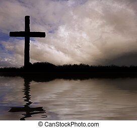 Silhouette of Jesus Christ crucifixion on cross on Good Friday Easter reflected in lake water