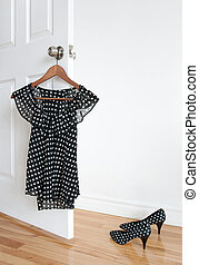 Polka dot blouse on a hanger and shoes on the floor - Black...