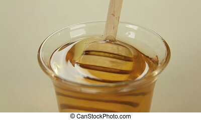 Profile Honey Twirler - Honey twirler is dipped into a glass...