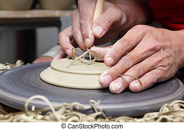 Potter's hands carving groove - Potter's hands carving a...