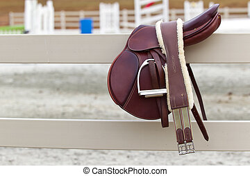 Riders Saddle - A dark english saddle sits on a fence with...