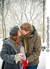 Kissing Couple While Snowing - young pair kissing outdoors,...