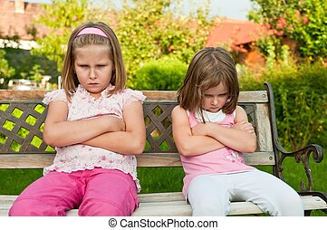 Quarrel - offended sisters - Small girls sisters siting on...