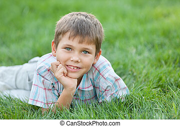 On the green summer lawn - A smiling boy is lying on the...