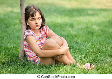 Boring girl sitting at the young tree - A pretty sad girl in...