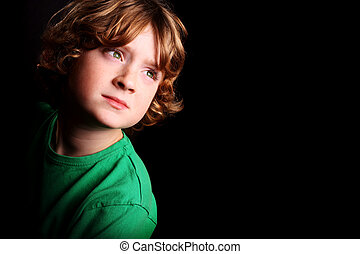 Cute young boy - A cute young boy looking upwards on a black...