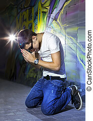 young man offers prayers in front of colorful graffiti wall