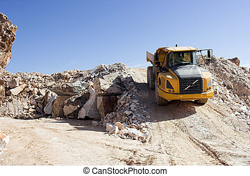 Heavy dump truck against blue sky operating in a marble...
