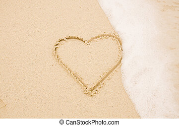 Heart on sand with wave - Handwritten heart on sand with...