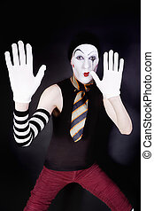 Funny mime on a black background with white gloves