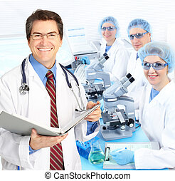 Laboratory - Science team working with microscopes in a...