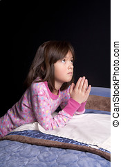 Saying prayers. - A young girl says her prayers just before...