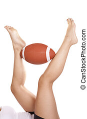 Legs up football - A woman laying on her back with her legs...
