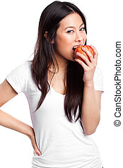 Asian woman eating apple - An isolated shot of a beautiful...