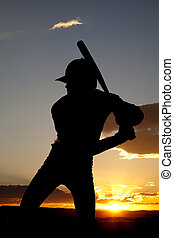 Silhouette baseball ready to swing sunset - A man standing...