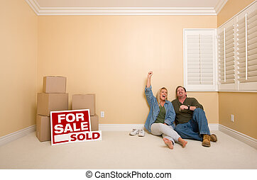 Couple on Floor Near Boxes and Sold Real Estate Signs -...