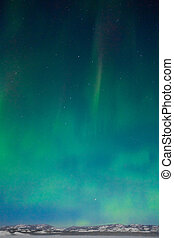 Northern Lights Aurora borealis over moon lit snowscape of...