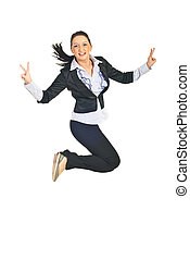 Victorious business woman jumping and showing victory sign...