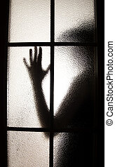 Girl behind the glass - black silhouette behind the glass as...
