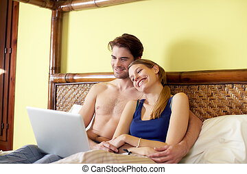 young couple lying on bed with pc - caucasian heterosexual...